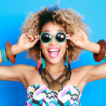 Curly-haired woman smiles against a blue wall while wearing sunglasses to welcome new patients to Megan Jones, DDS
